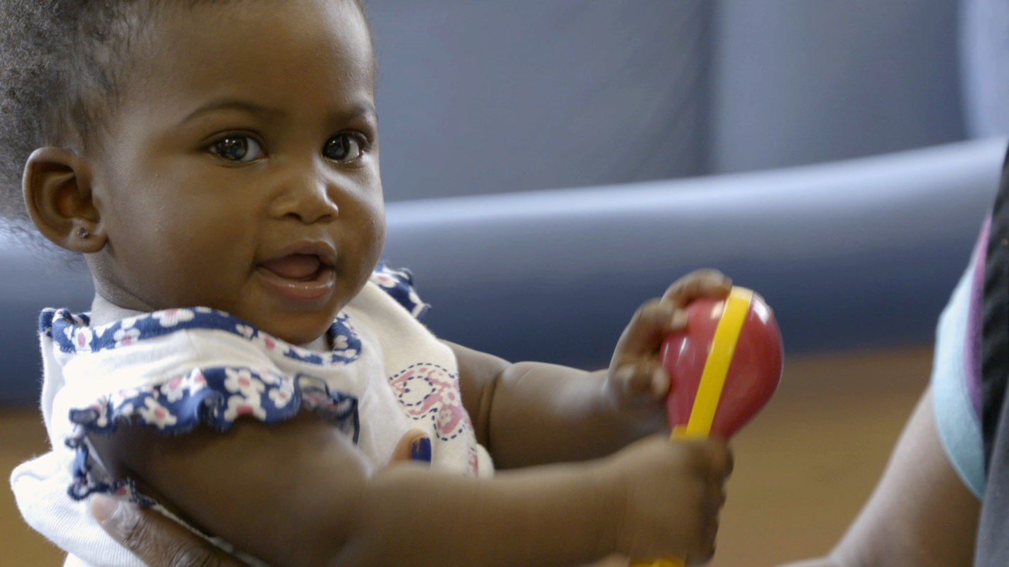 A girl plays in the infant room at Sheltering Arms.